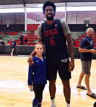 US Olympic gymnast standing beside an Oplympic basketball player.